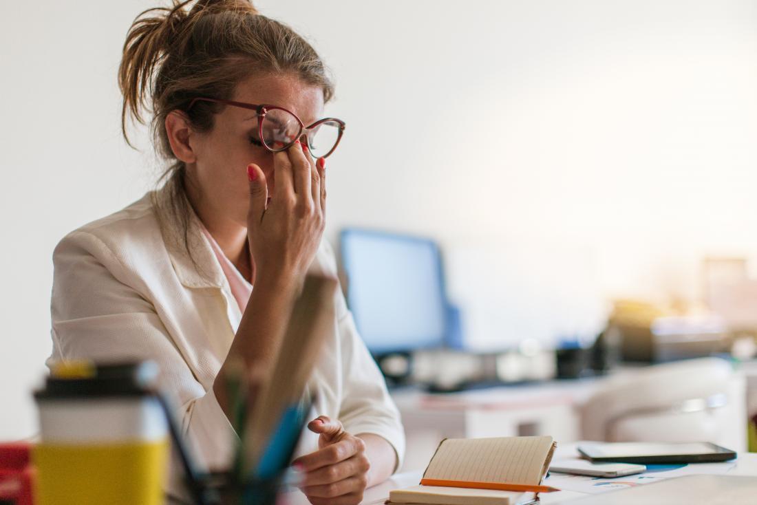 Femme stressée et fatiguée, se frottant les yeux au travail.