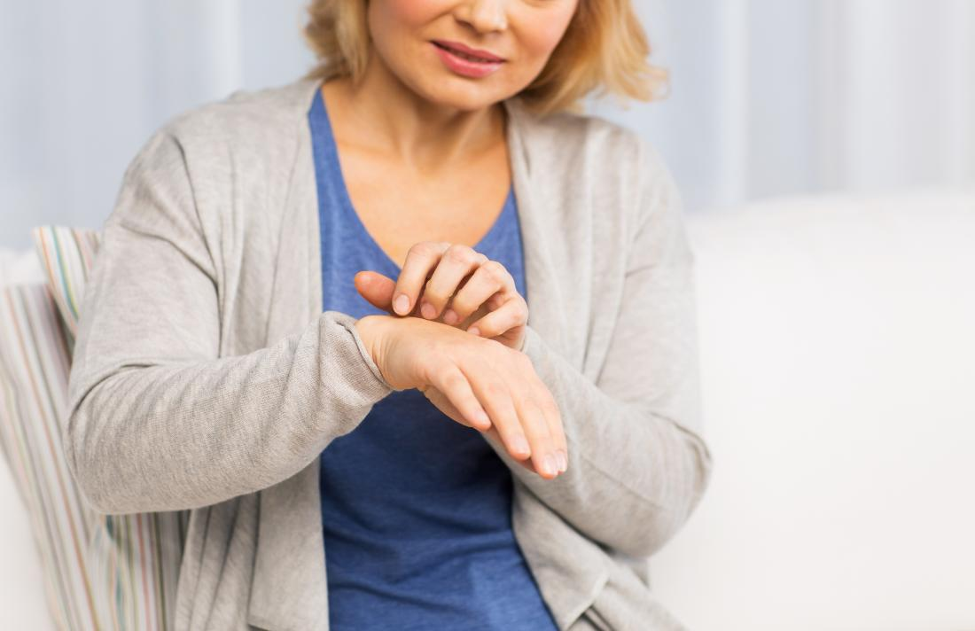 older woman scratching her hand with a menopause rash