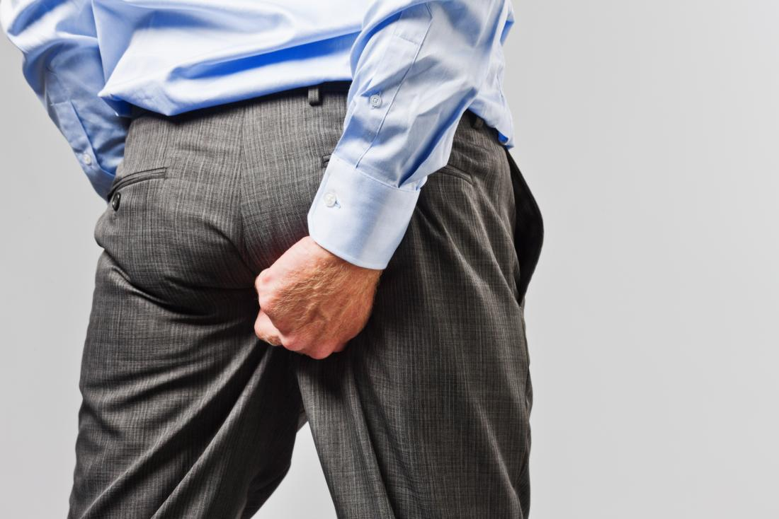Man in business suit with butt rash scratching his bottom.