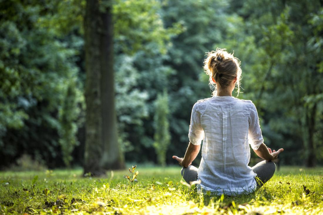 Woman meditating in the forest which may be a way to stop heart palpitations