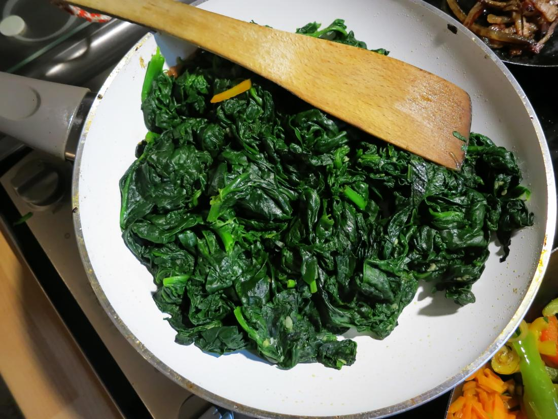 Cooked spinach on a plate is a food high in vitamin k