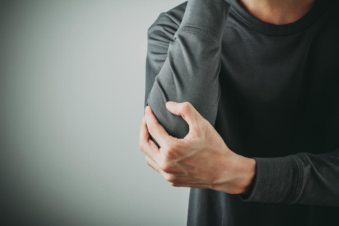 man holding his elbow in pain due to a hyperextended elbow