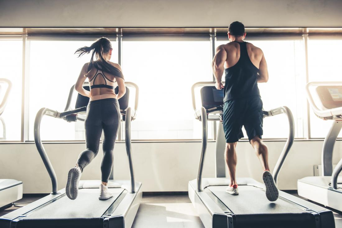 Man and women next to each other on running machines in gym,