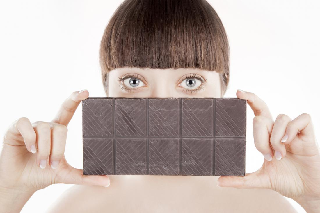 a woman holding a bar of dark chocolate