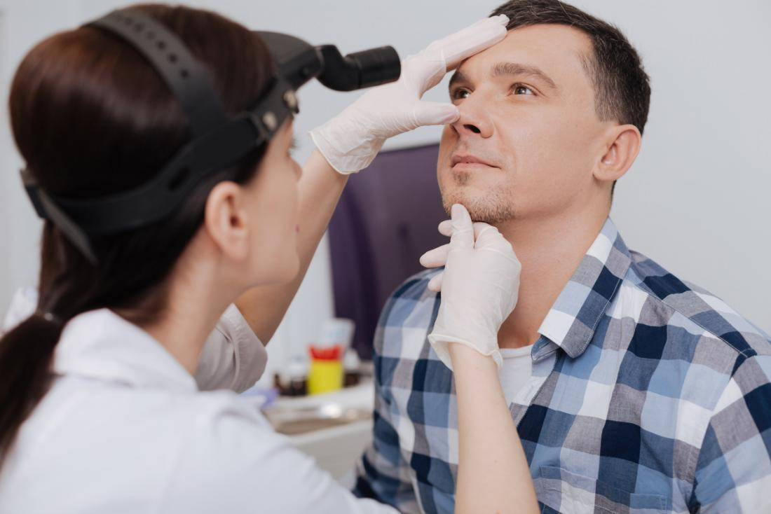 Female doctor inspecting man's nose for cause of tickling.