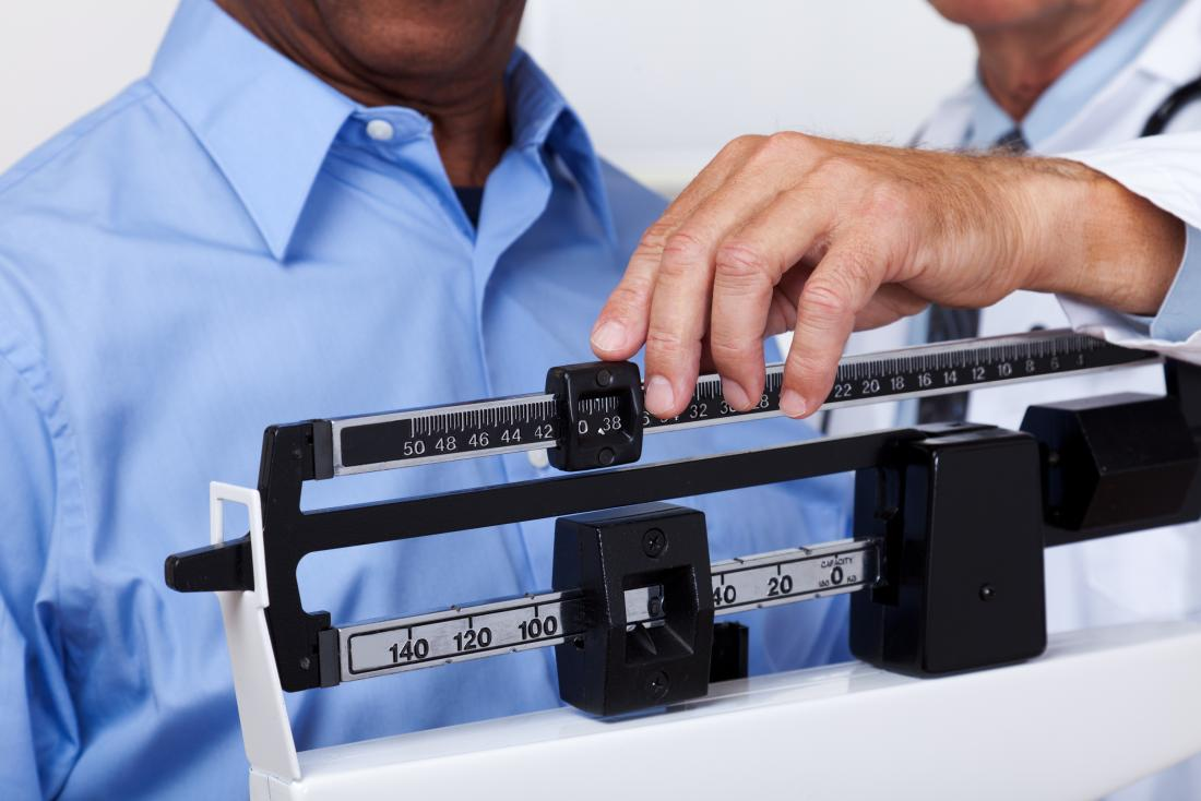 Man on weighing scale with doctor.