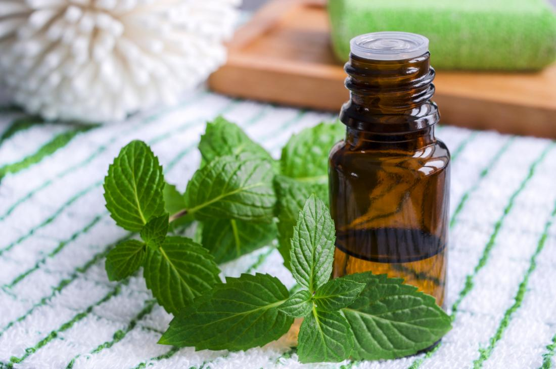 peppermint leaves next to small bottle of essential oil.