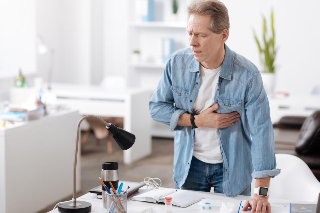 Man at desk at work clutching his chest because of heart pain.
