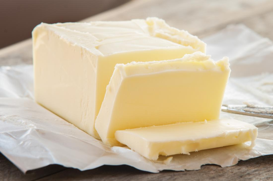 Block of butter on wrapper partially sliced.