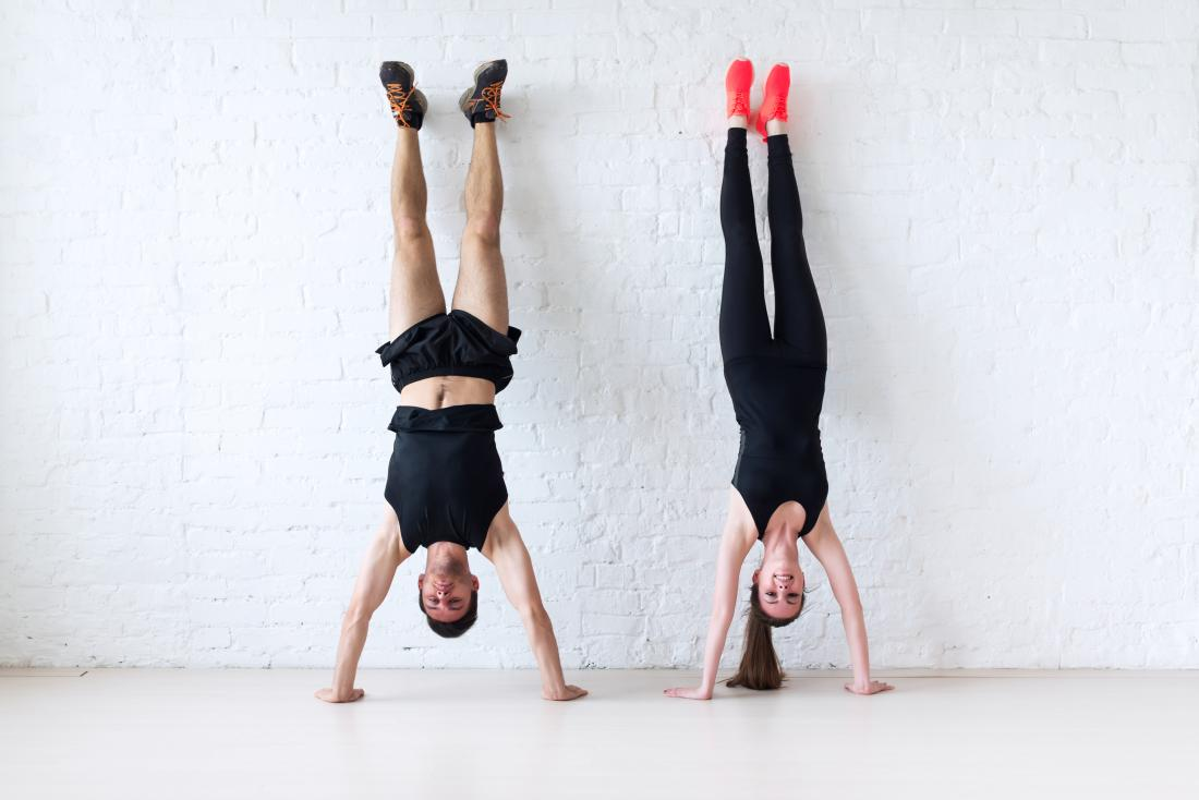 Couple doing handstand against wall.