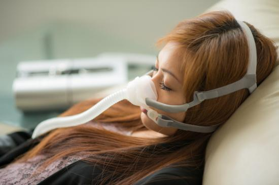 Woman with sleep apnea using cpap machine