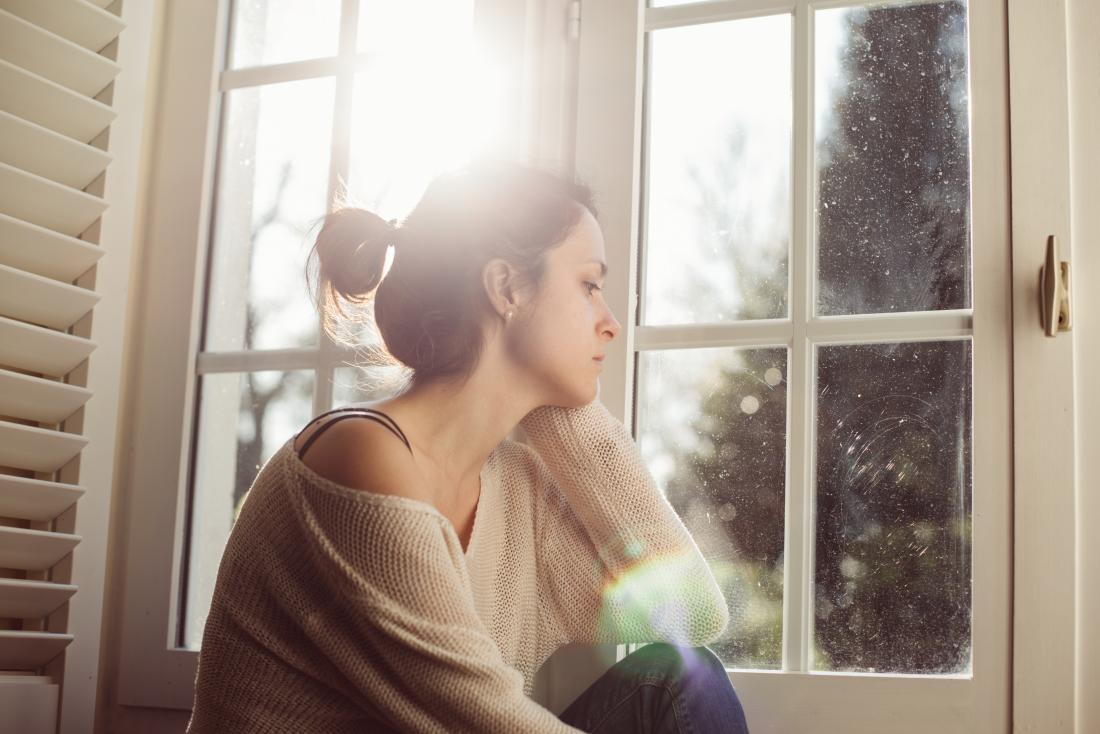 Anxious woman looking out of the window worrying about female prostate cancer