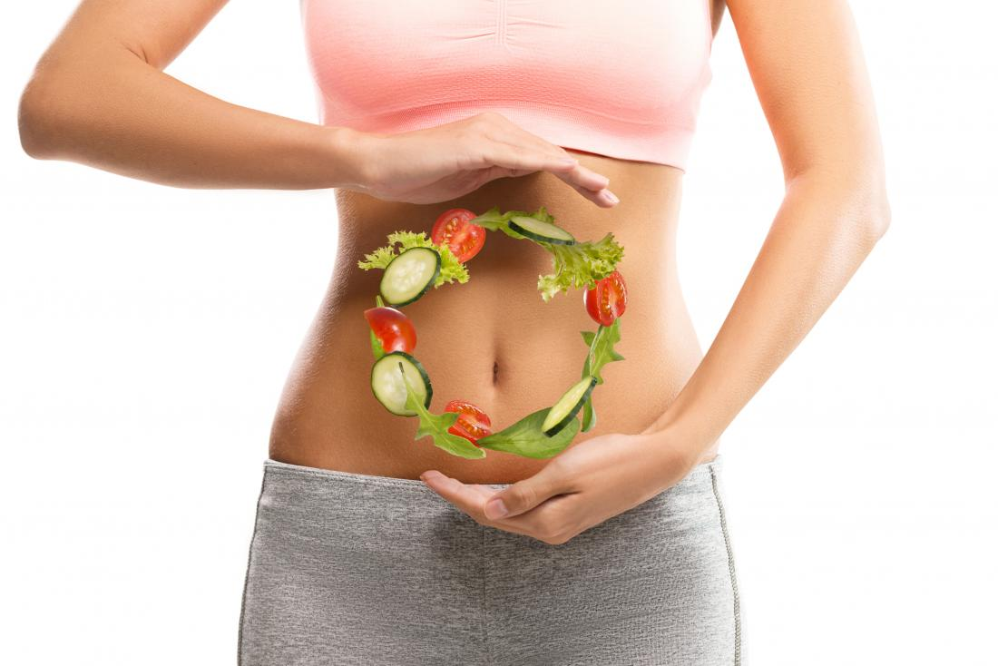 woman with vegetables hovering in front of her belly