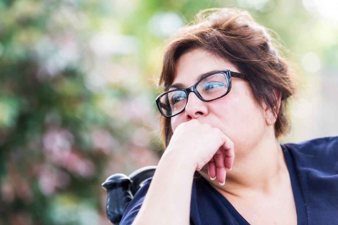 Mature woman outside looking contemplative considering estrogen and weight gain