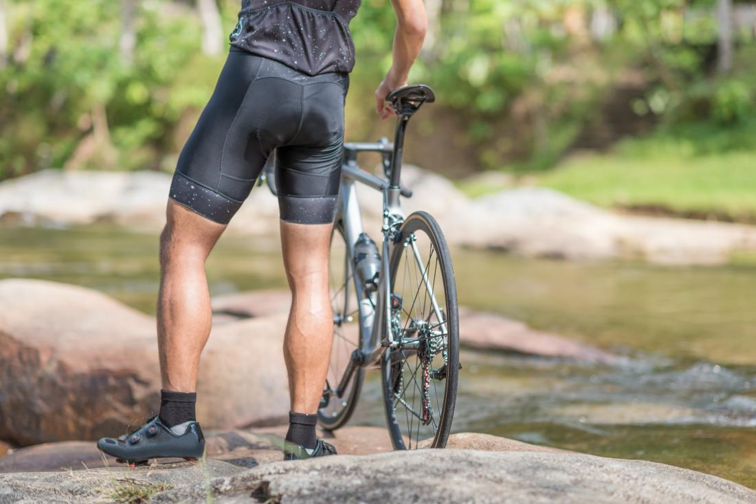 Man with bike wearing cycling shorts showing muscular legs.