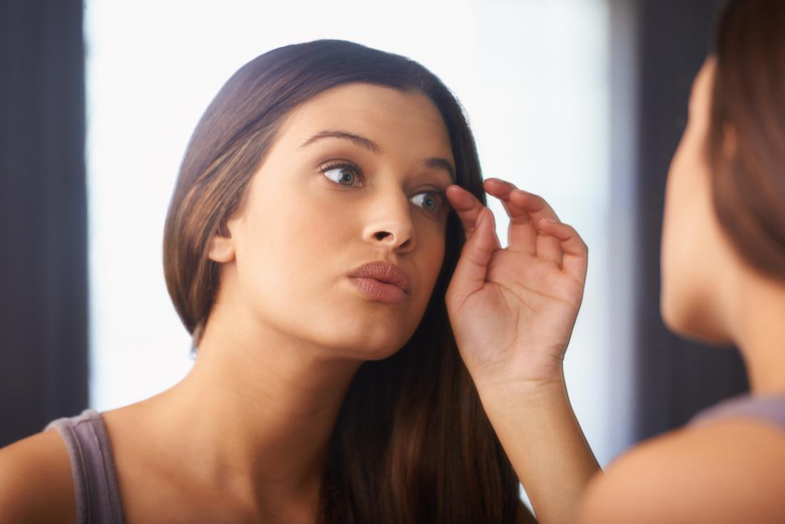 Woman looking in the mirror wondering if eyelashes grow back