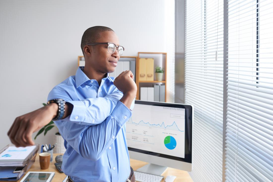 Man standing up in office stretching his arms and shoulders.