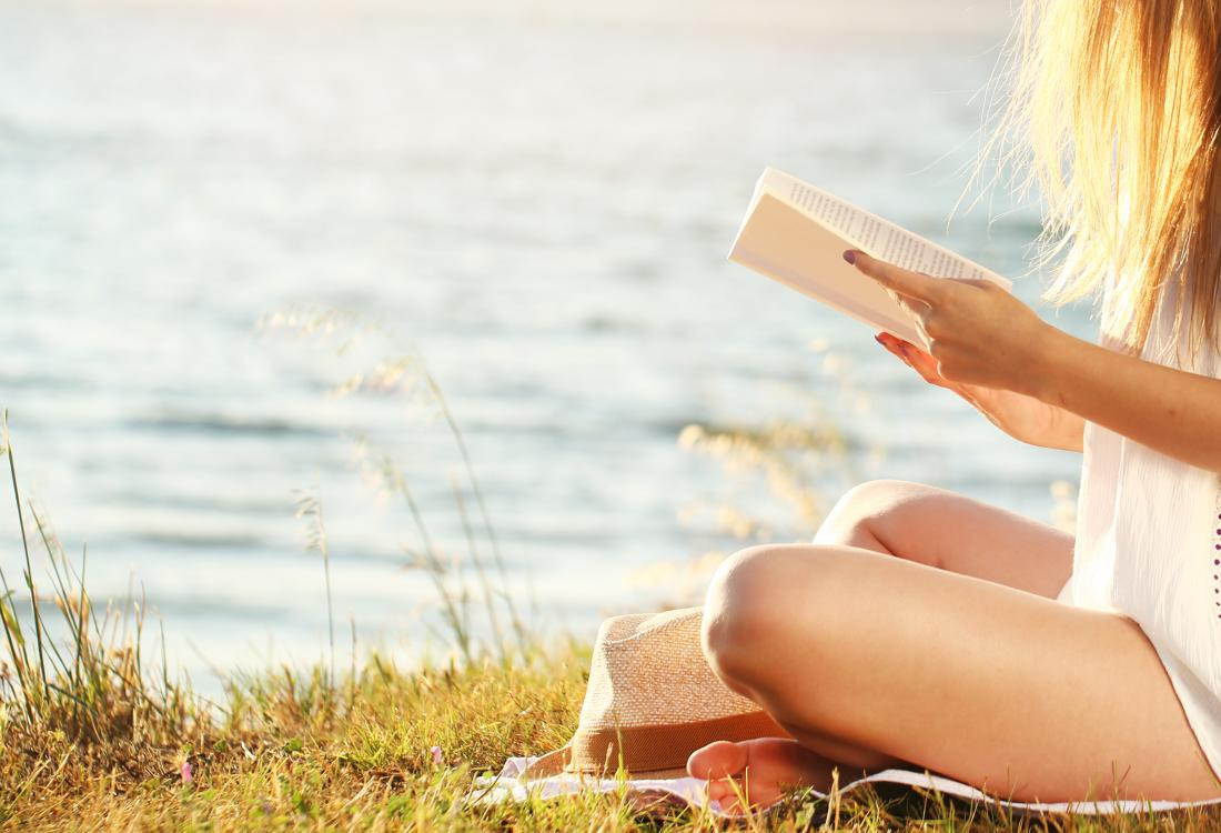 Woman reading in the sun for vitamin d to help with joint pain