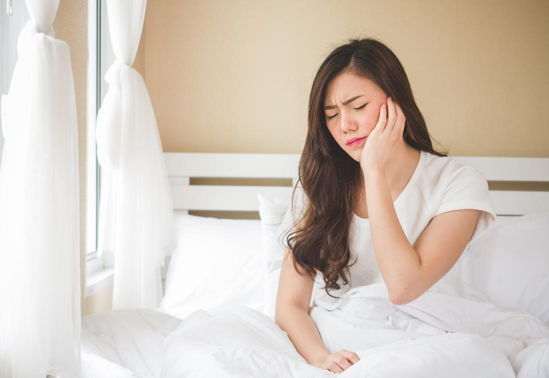 Woman holding side of jaw and face because of eagle syndrome pain, while sitting in bed.