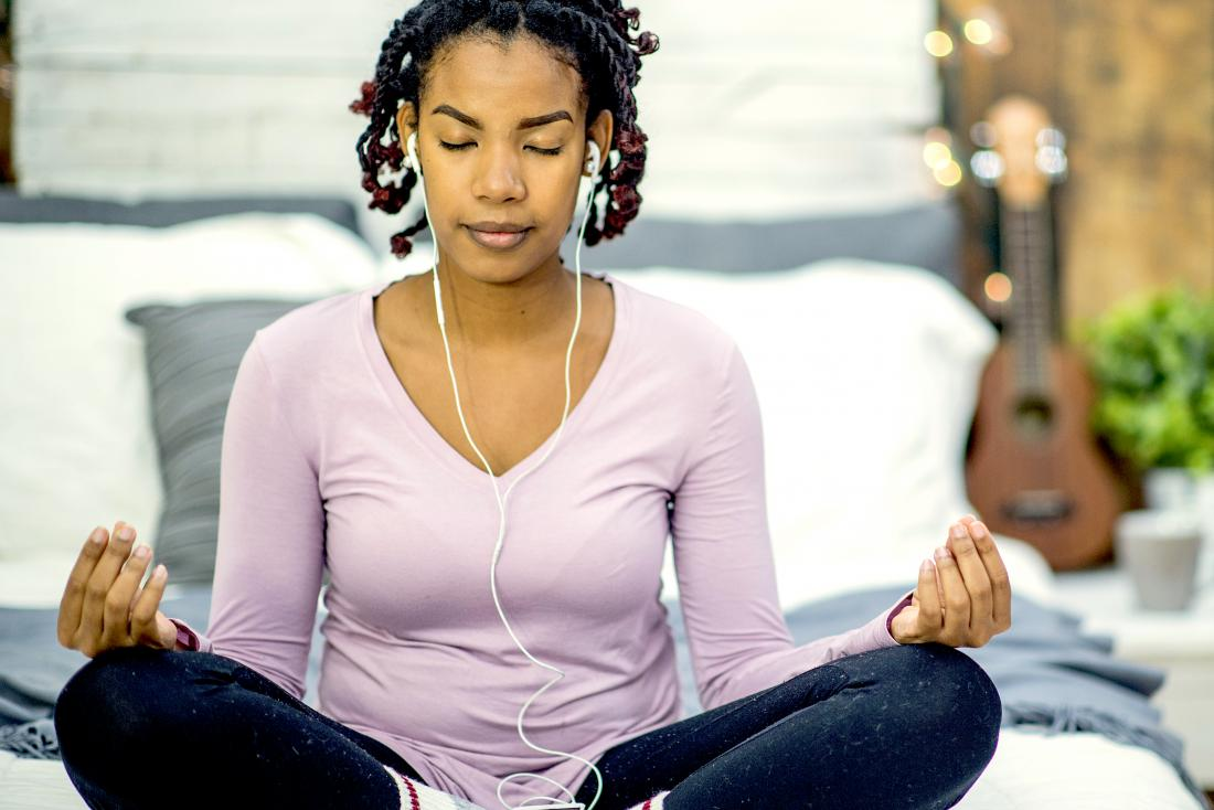 Woman meditating and sitting cross-legged on bed with headphones in as a natural remedy for PMDD