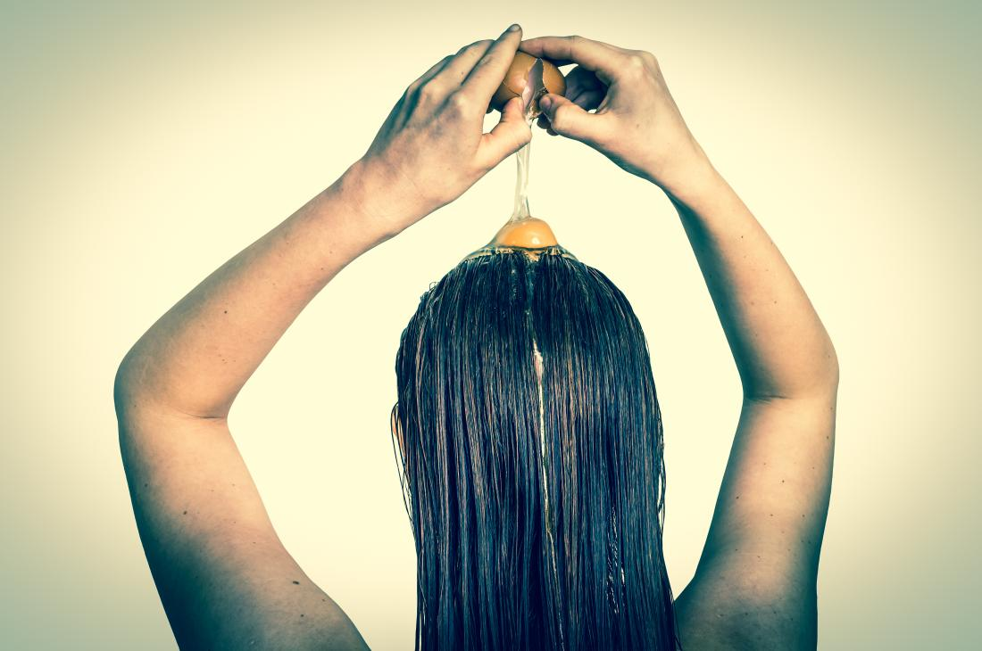 Woman cracking an egg and its yolk onto her hair