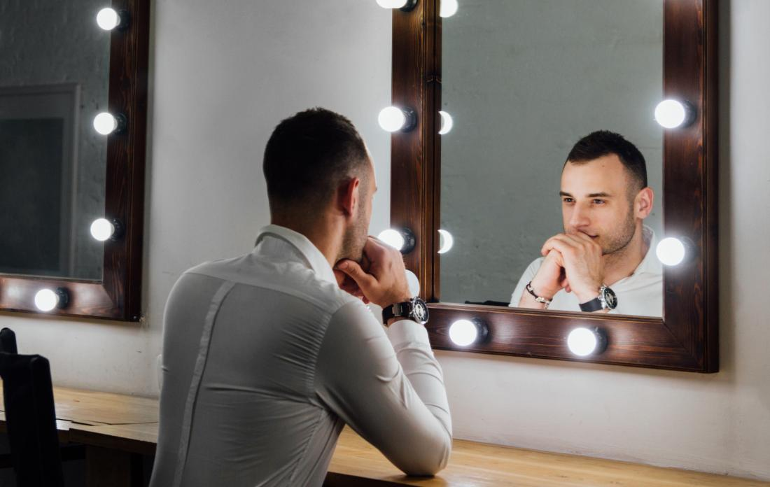 Man with bipolar and narcissism sat in front of mirror in bright lights.
