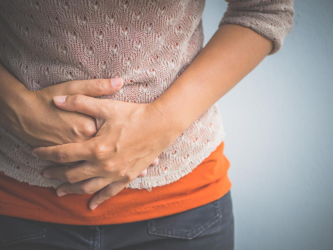 Woman holding stomach due to chronic gastritis