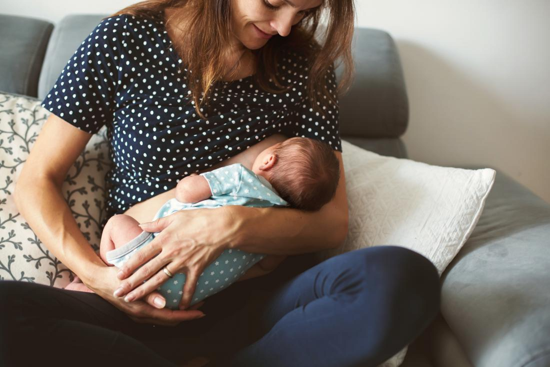 Woman with breast cancer breast-feeding baby.