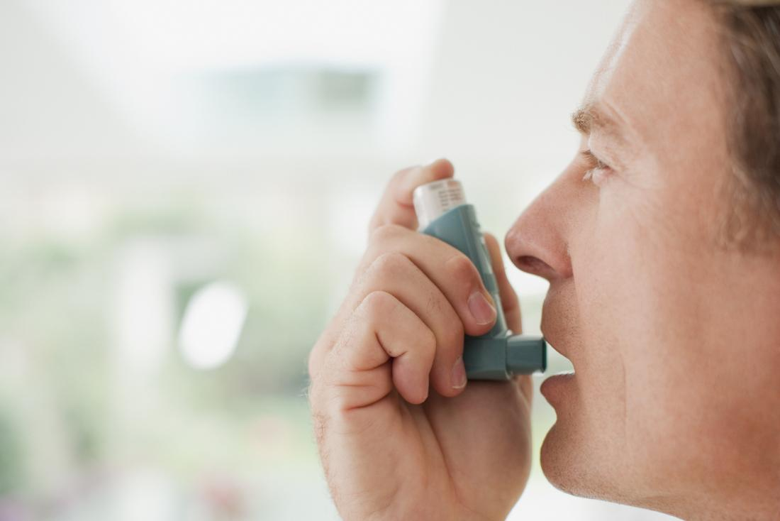 Man with asthma using an inhaler
