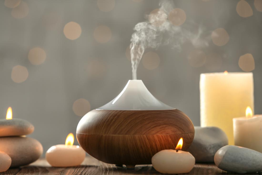 Essential oil aromatherapy diffuser surrounded by candles.