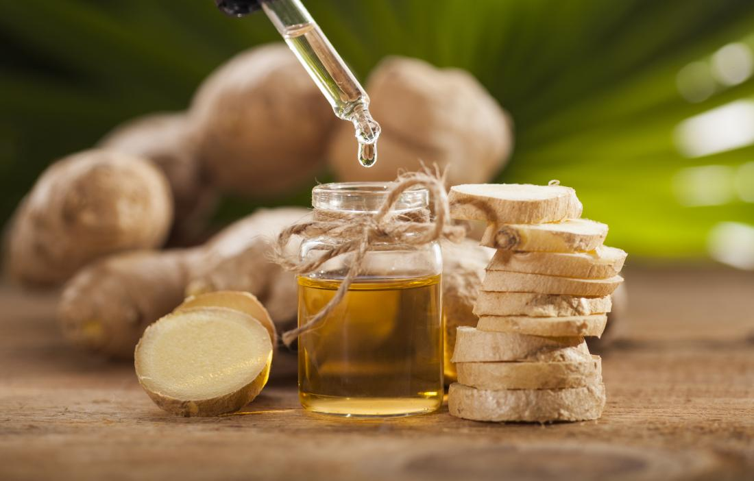 Ginger essential oil in bottle next to sliced ginger for treating nausea