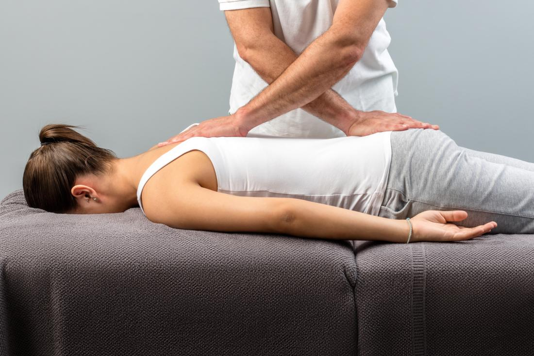 Chiropractor working on woman's back