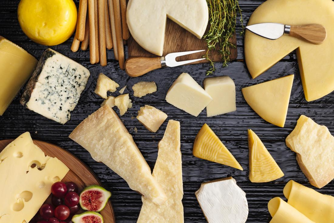 A variety of cheeses on a wooden table for article about cholesterol.