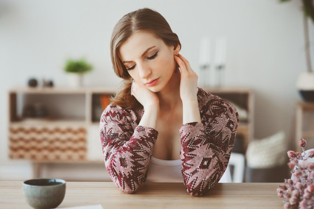 tired young woman sitting in kitchen