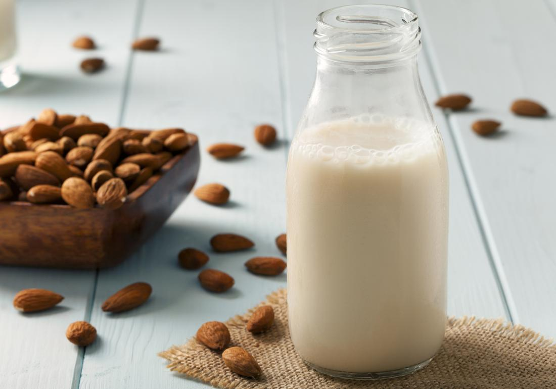 Almond milk in glass bottle on wooden table with bowl of almonds spilling out.