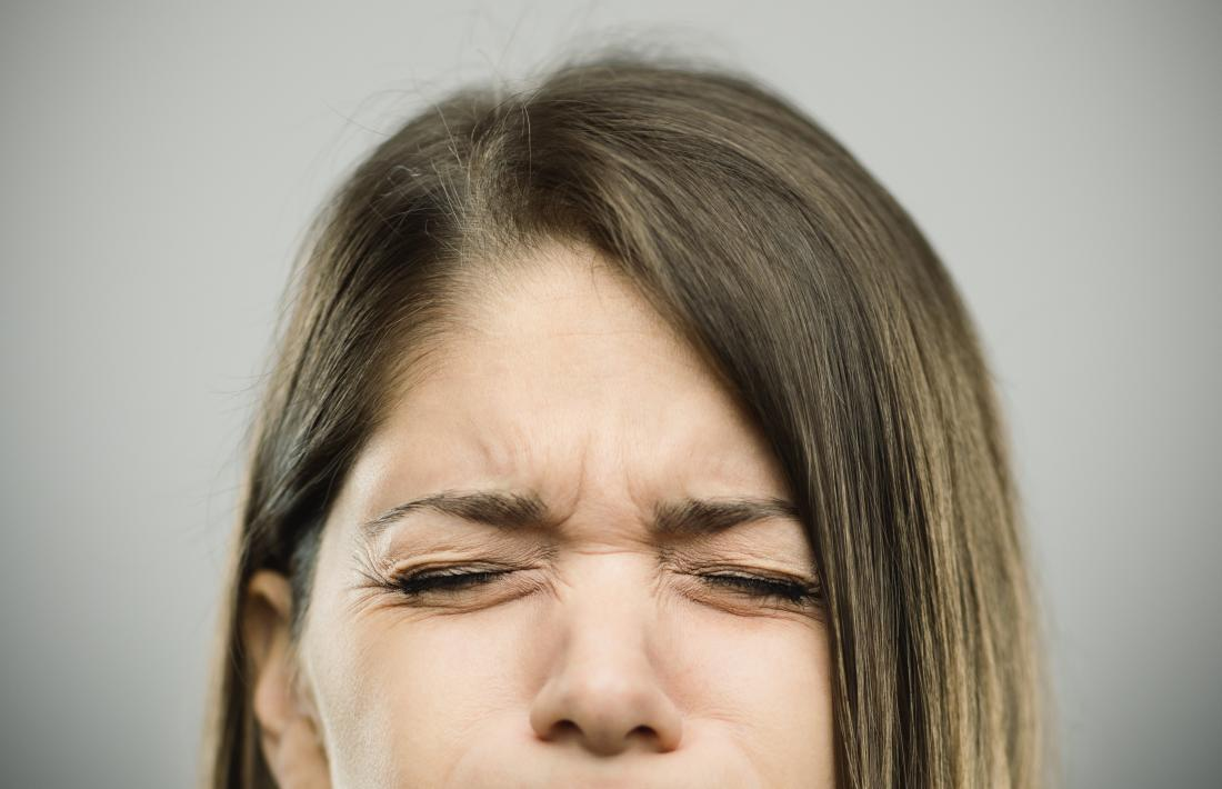 woman screwing eyes up in pain