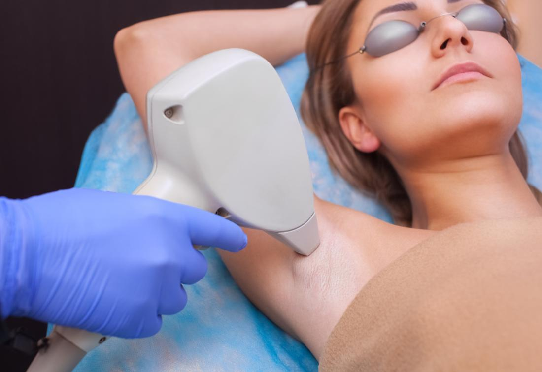 Woman having laser hair removal on her armpit