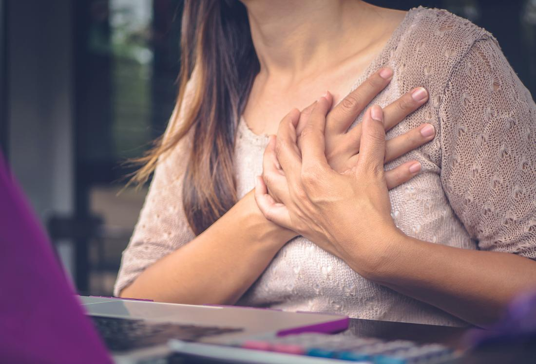 Woman with chest pains clutching her chest while sitting at desk.