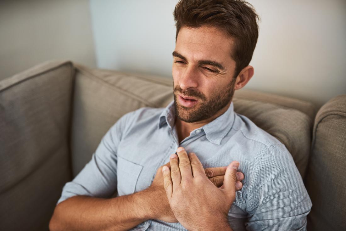 Man with stable angina experiencing chest pain while sitting on sofa.