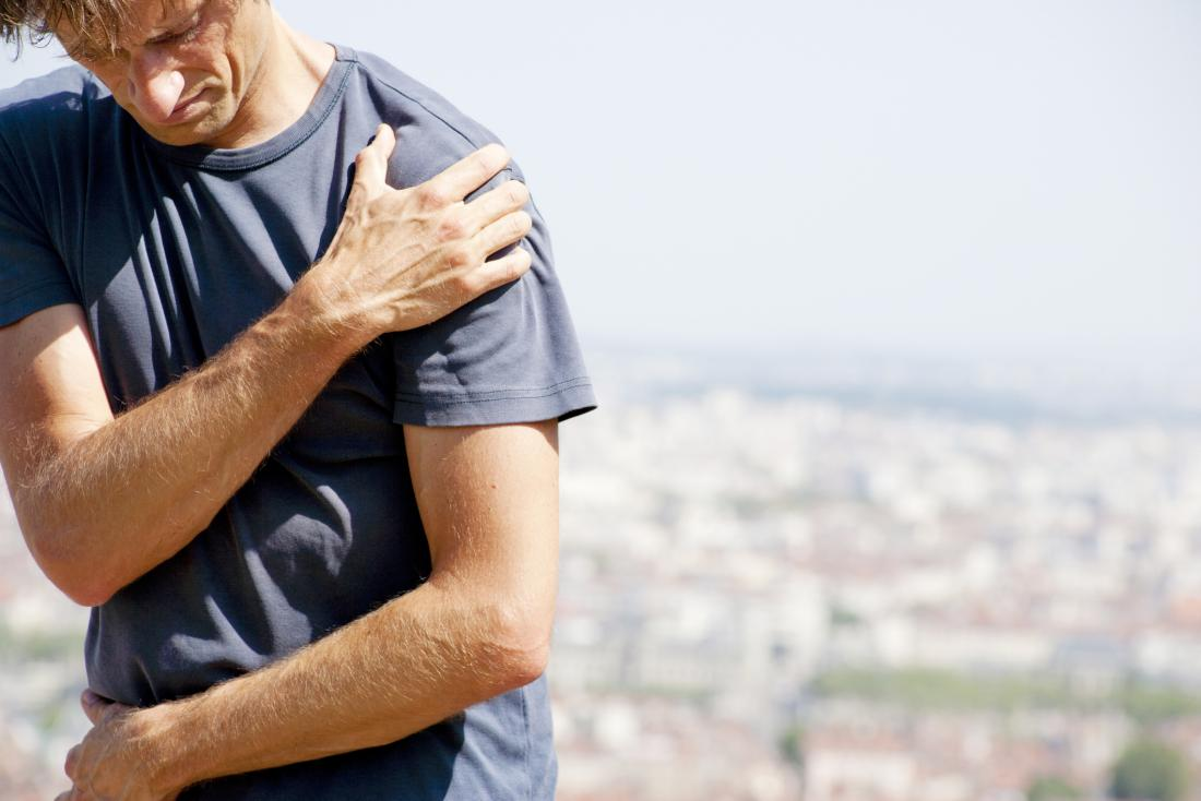 man holding his shoulder due to rotator cuff tendinitis