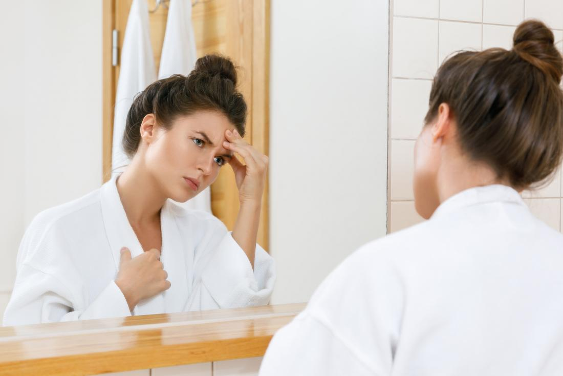 Woman with chest pain and headache looking in bathroom mirror in dressing gown
