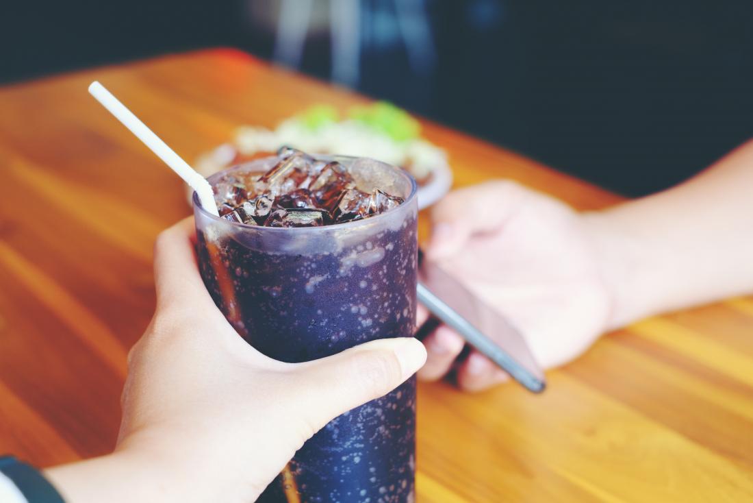 يد تمسك كأس الكولا