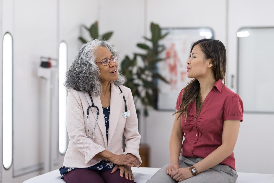 Woman sitting on bed in doctors office speaking to female GP.