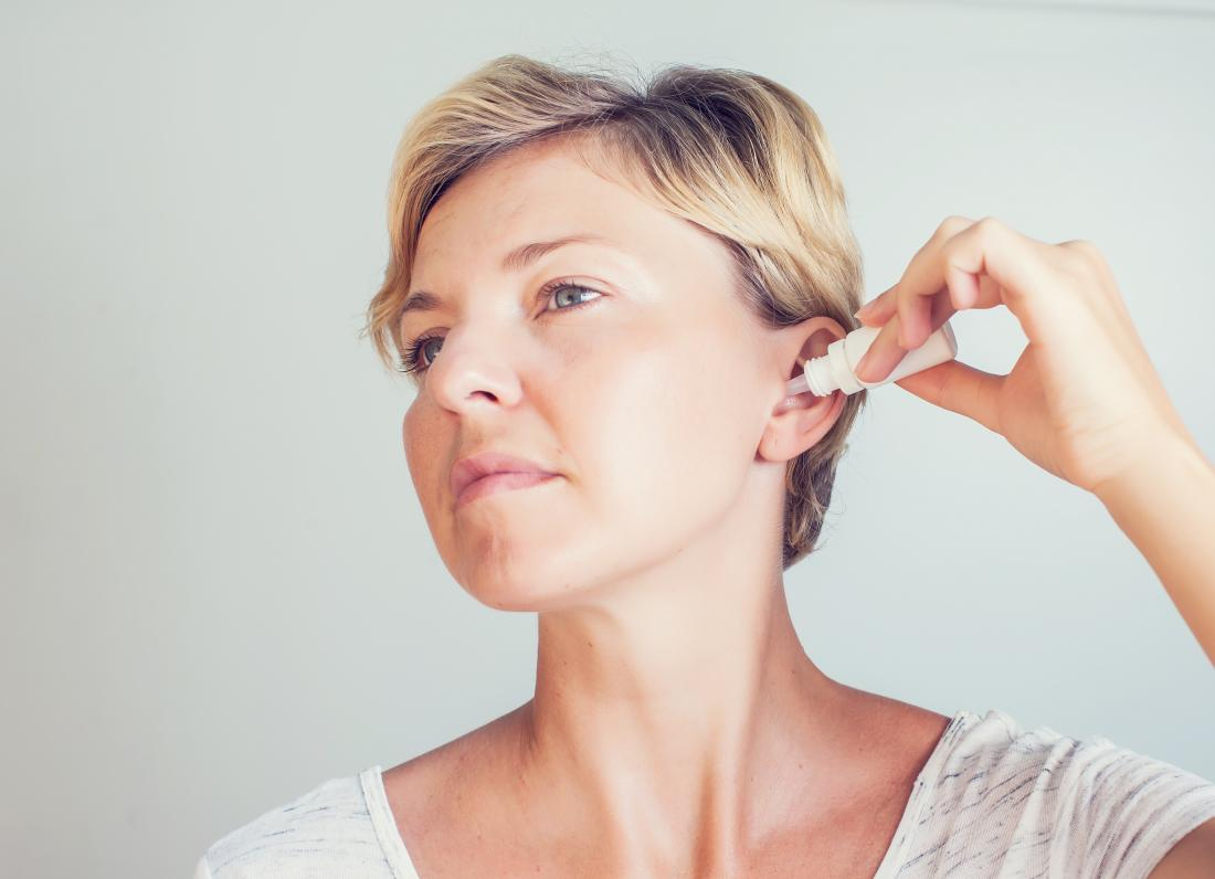 Woman using ear drops to remove built up ear wax