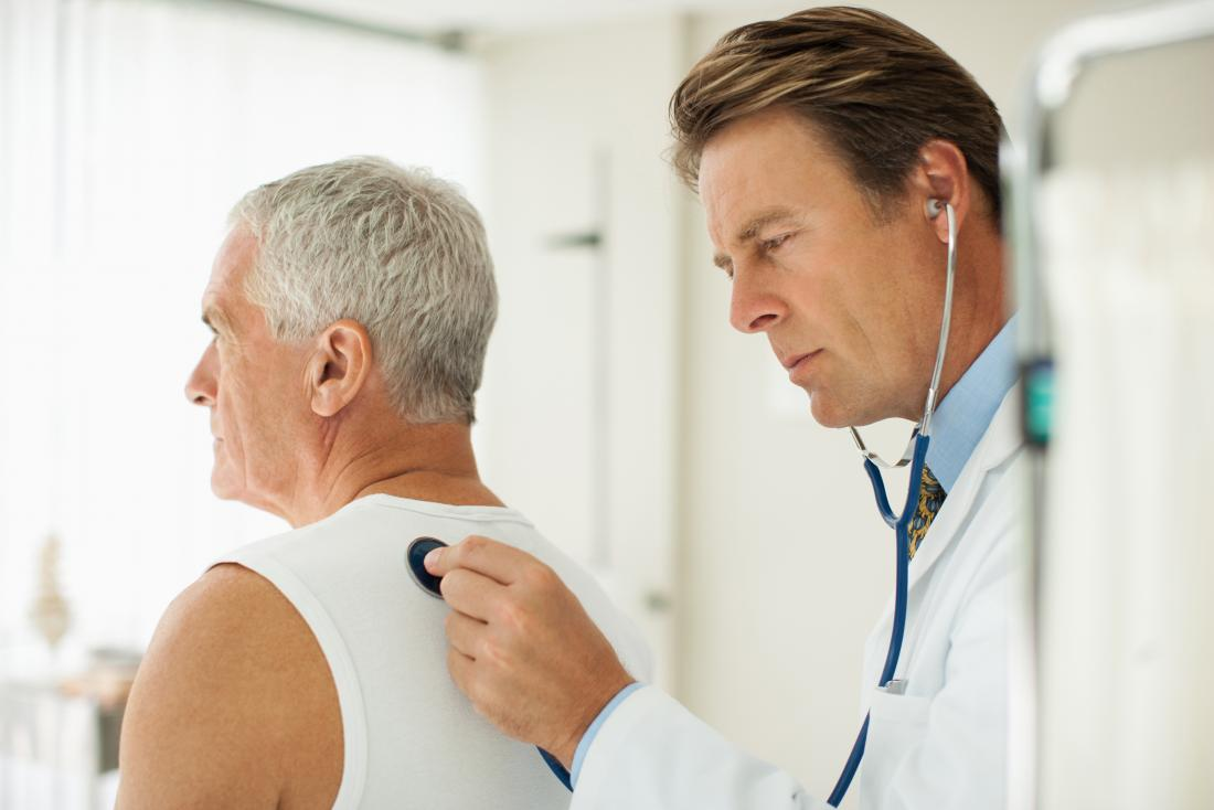Doctor using stethoscope to listen to sounds of man breathing.