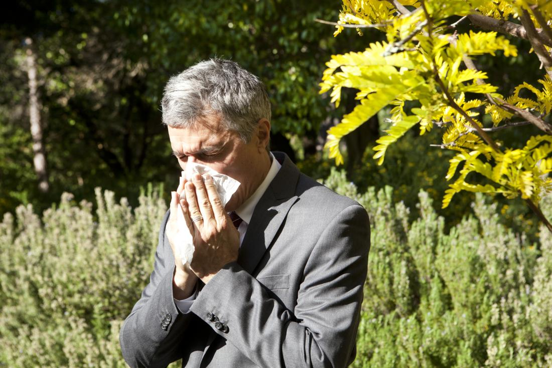 Man blowing his nose outdoors because of pollen allergy.