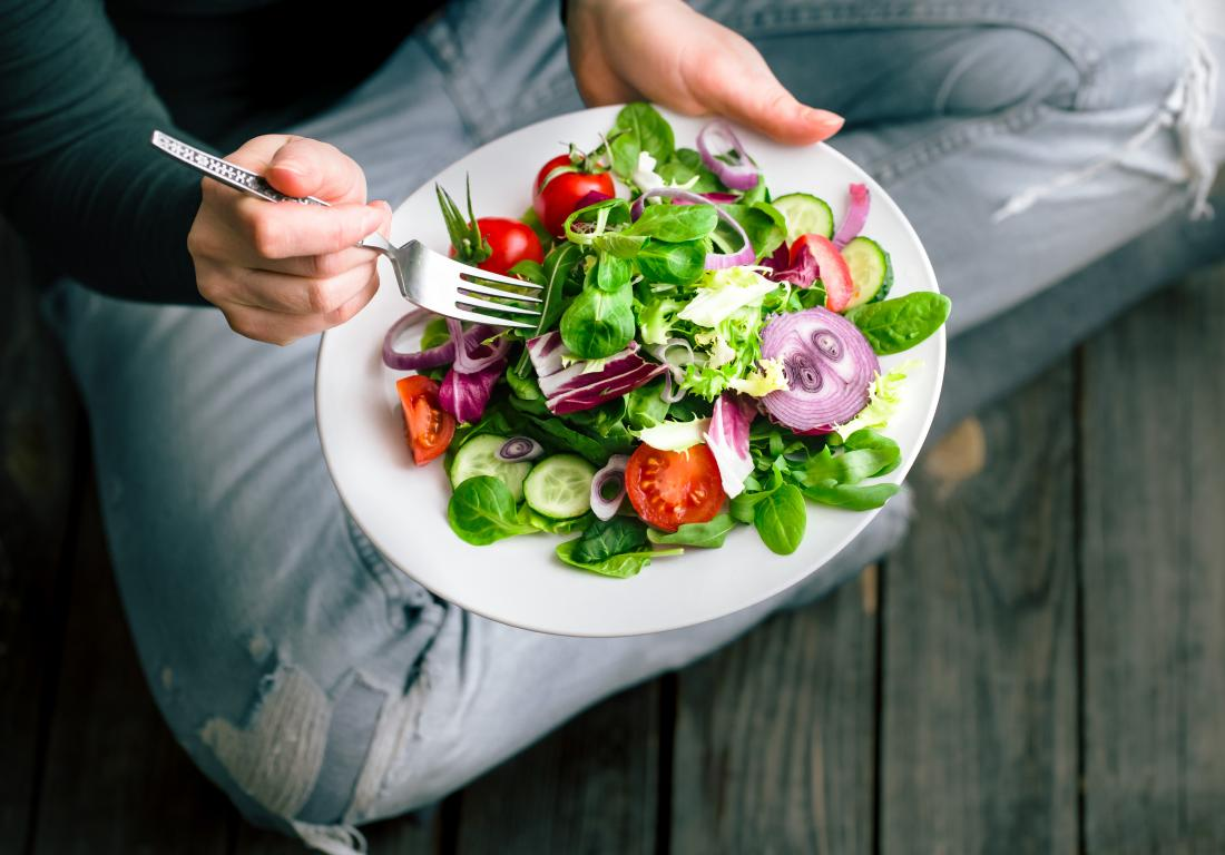 a person sitting on the floor eating a healthy salad