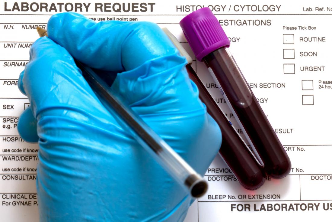 Differential blood test paperwork from lab being filled out by gloved hand next to blood sample vials.