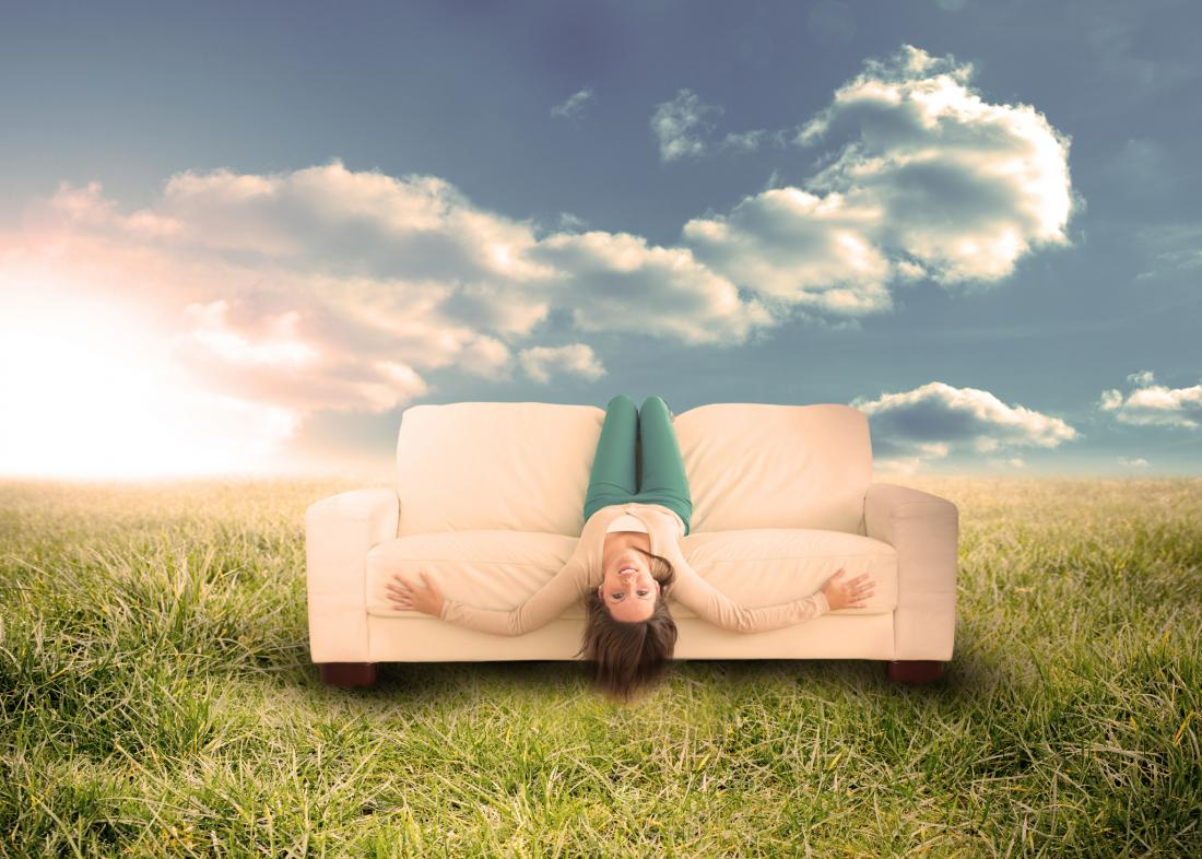 concept illustration of a woman sitting upside down on a sofa in nature