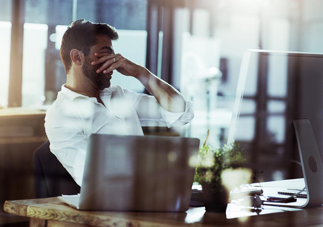 Stressed man at work wondering about ways to lower cortisol